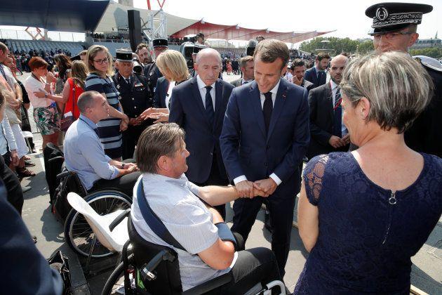 Emmanuel Macron serre la main d'un policier blessé, sur les Champs-Élysées le 14
