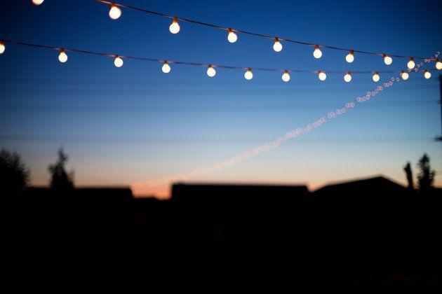 String lights hang outdoors on a summer evening.