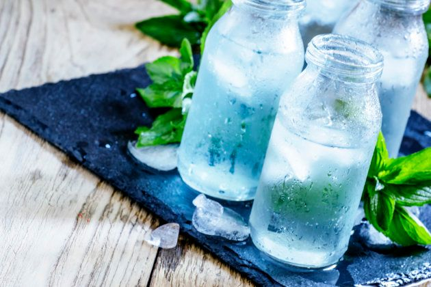 Very cold mineral water with ice in a misted glass bottles, dark background, selective focus