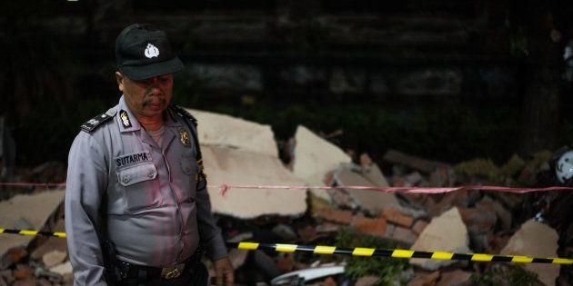 Un policier devant les ruines d'un immeuble à Bali, après le nouveau séisme à Lombok, le 5