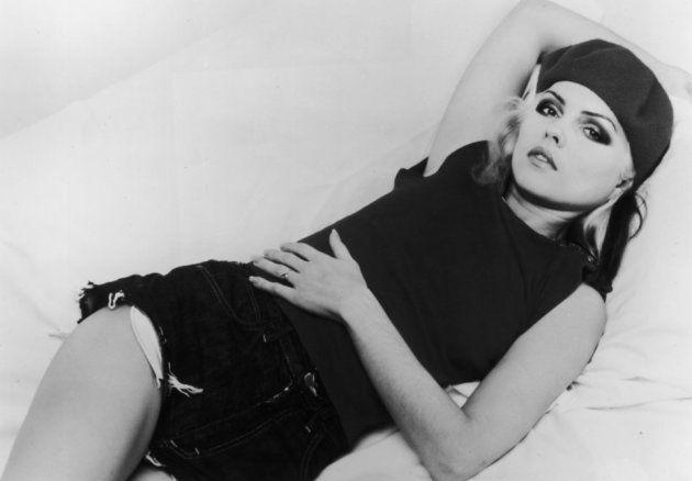 Un portrait en studio de la chanteuse de Blondie allongée sur un lit en 1977.