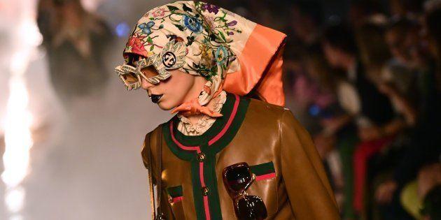 Une mannequin défile, entre les flammes, au défilé croisière Gucci, au mois de mai, à Arles.