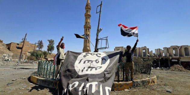 Des membres des Unités de mobilisation populaire descendent le drapeau de Daech dans la ville de Tal...