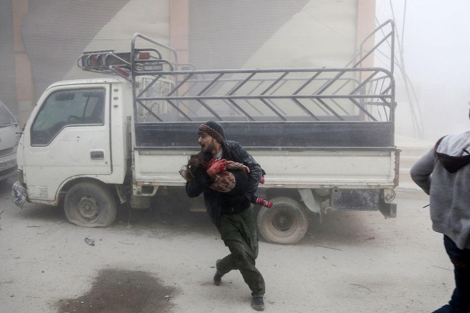 6 février - Un homme portant un enfant alors qu'il fuit les frappes aériennes syriennes qui auraient...