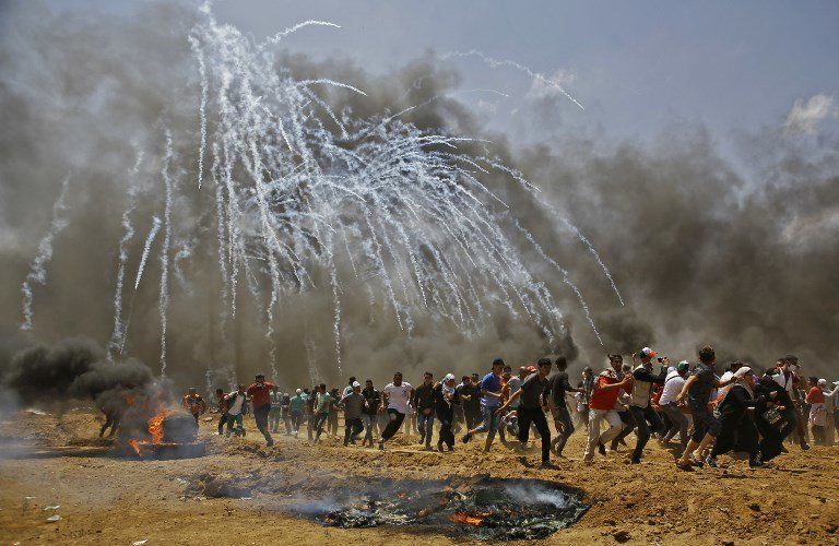 14 mai - Des Palestiniens cherchent à se protéger de gaz lacrymogènes lors d'affrontements avec les forces...