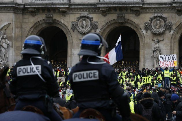 TOPSHOT - French mounted police stand in front protesters wearing yellow vests (gilets jaunes) during...