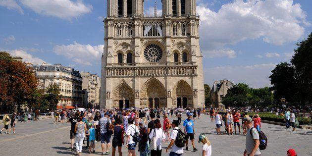 Des touristes devant Notre-Dame de Paris le 8 août