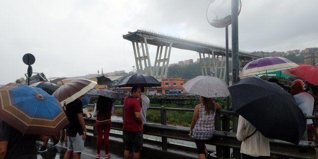 Des curieux observent les opérations de secours après l'effondrement du pont