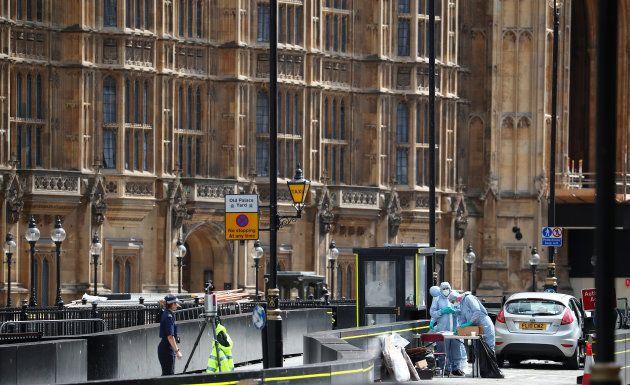Des enquêteurs autour de la voiture de l'homme qui a foncé dans les barrières du Parlement ce mardi 14...