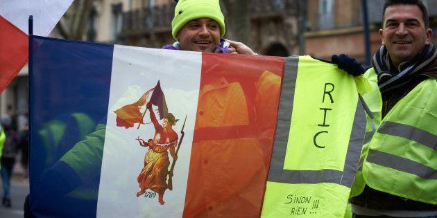 Des gilets jaunes brandissent un drapeau français réclamant le RIC, le 15 décembre 2018 à
