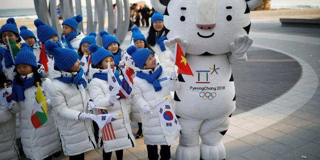 Des enfants photographiés le 8 février 2018 avec la mascotte des Jeux Olympiques de Pyeongchang. REUTERS/Kim
