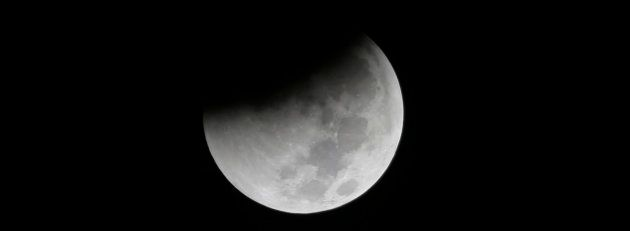 Earth starts its shadow on the moon during a complete lunar eclipse over Saturday Aug. 28, 2018 in Jakarta,...