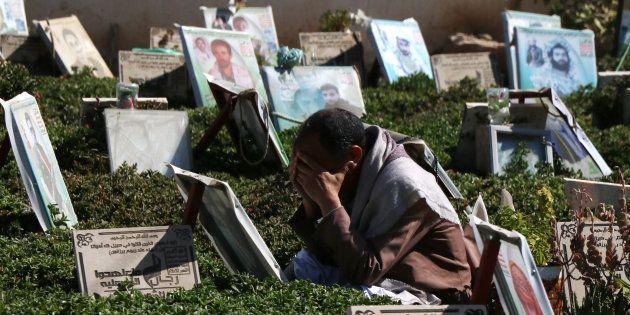 Un homme pleure l'un de ses proches mort à la guerre, dans un cimetière à Sanaa, au Yémen, le 21 décembre