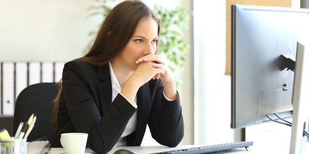 Concentrated businesswoman trying to solve a difficult assignment on line in a desktop computer at