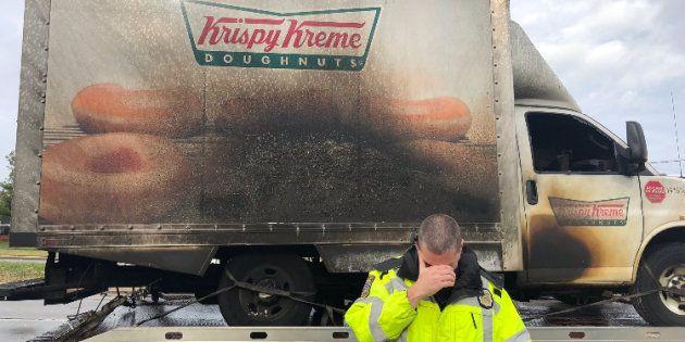 Un officier de la police de Lexington la tête baissée devant le camion incendié de la société de donuts...