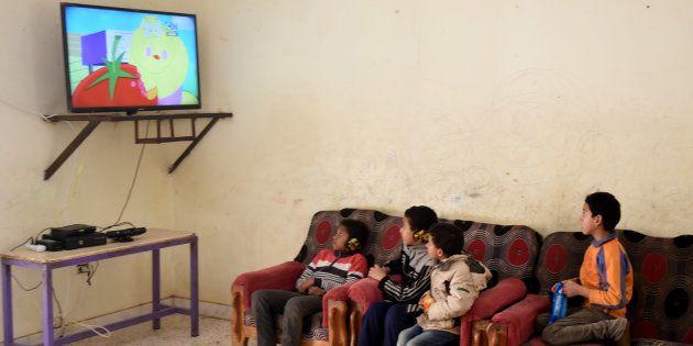 Des enfants égyptiens regardant la télévision au Caire, en février