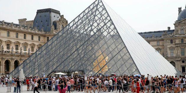 Des touristes font la queue devant la pyramide du Louvre en juillet