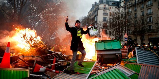 Un manifestant sur une barricade en flammes lors de l'acte VIII des gilets jaunes à Paris, samedi 5