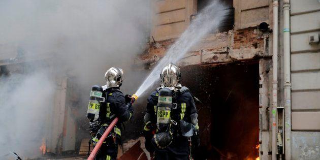 Des pompiers intervenant à la suite de l'explosion qui a coûté la vie à quatre personnes, dont deux soldats...