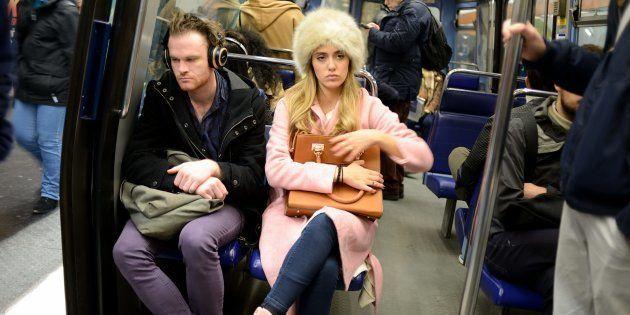 Des voyageurs assis sur des strapontins dans le métro de Paris en juin
