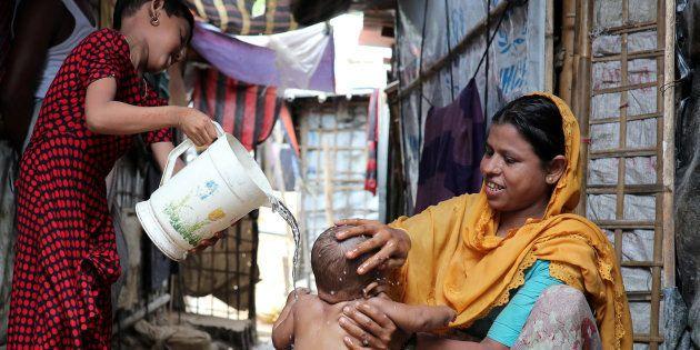 Une réfugiée rohingya lave son fils dans le camp de Cox's Bazar, au
