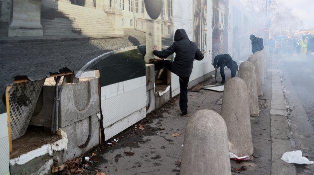 Des manifestants cagoulés tentent de forcer la palissade donnant accès à l'Assemblée