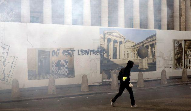 Un manifestant passe devant la palissade barrant l'accès aux marches de l'Assemblée