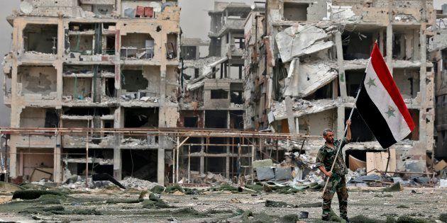 Un membre des forces pro-gouvernementales syriennes devant des bâtiments endommagés dans le camp de réfugiés...
