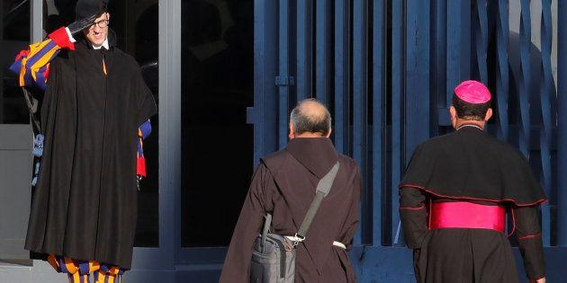 Les gardes suisses du Pape saluent deux participants arrivant au sommet du Vatican consacré à la