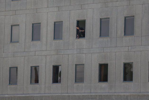 Un policier iranien à la fenêtre du bâtiment du Parlement iranien pendant la fusillade, le 7