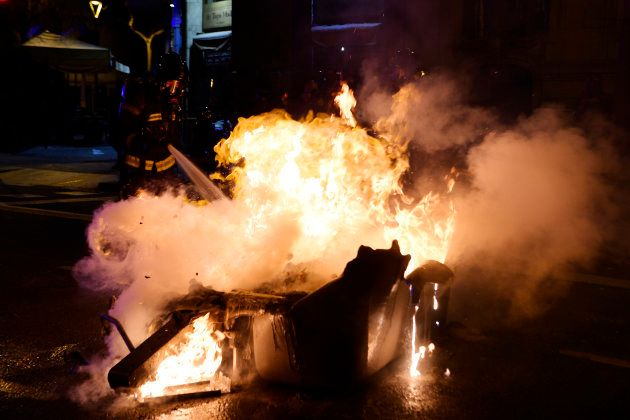 A firefighter douses a burning trash container during clashes between riot police and demonstrators in...