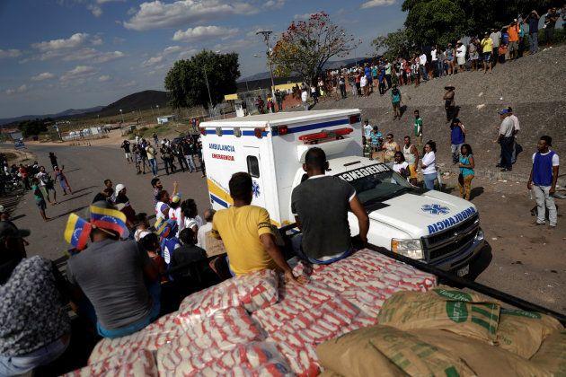 Une ambulance transportant des blessés vénézuéliens passe près d'un camion d'aide humanitaire, à Pacaraima,...