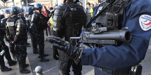 Un officier de police avec un lanceur de balle de défense lors d'une manifestation de gilets jaunes à...