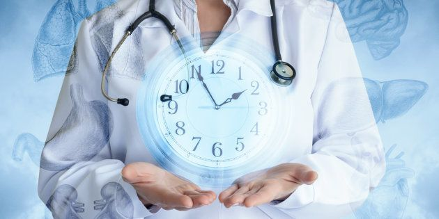 Doctor shows the clock on the background of internal organs and the