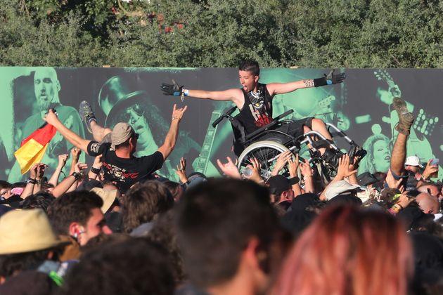 Un festivalier en fauteuil roulant porté par la foule au Hellfest le 16