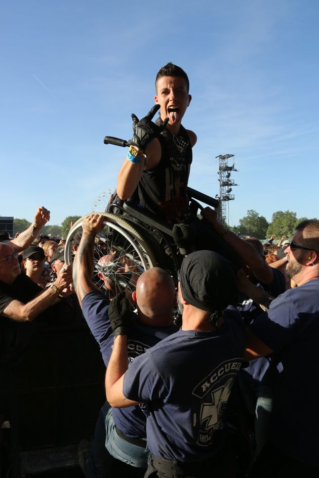 Un festivalier en fauteuil roulant porté par la foule au Hellfest, le 16