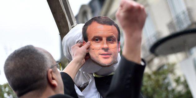 Un homme frappant le mannequin à l'effigie du président Macron pendant une manifestation à