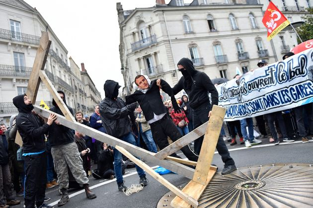 Protestors carry an effigy of French President Emmanuel Macron during a demonstration calling for a union...
