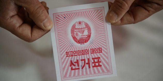 Un responsable tenant un bulletin de vote dans un centre de vote à Pyonyang, lors du vote pour les élections...