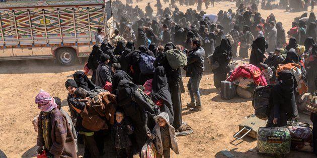Des femmes et des enfants évacués de Baghouz, dernière enclave contrôlée par Daech en Syrie, se rendant...