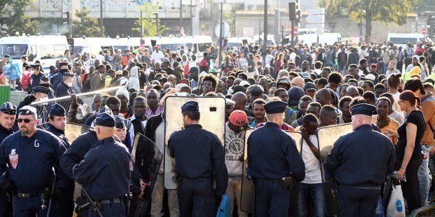 Des policiers font face aux migrants pendant l'évacuation d'un camp sauvage à la porte de la Chapelle...
