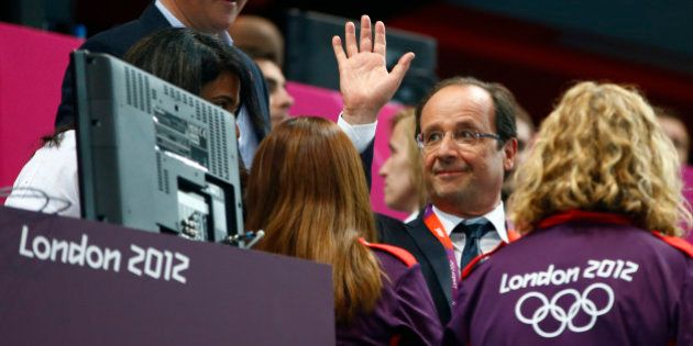 France's President Francois Hollande waves as he is accompanied to his seat by British Prime Minister...