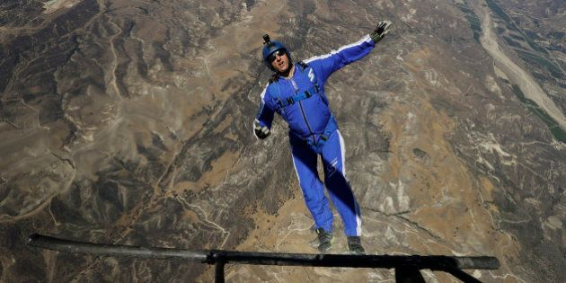 In this Monday, July 25, 2016 photo, skydiver Luke Aikins jumps from a helicopter during his training...