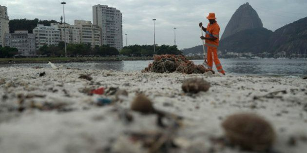 A clean workers removes the trash over the sand of Botafogo beach next to the Sugar Loaf mountain and...