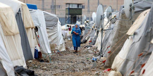 Une réfugiée syrienne marche entre les tentes dans le camp de réfugiés de Nizip, près de la frontière...