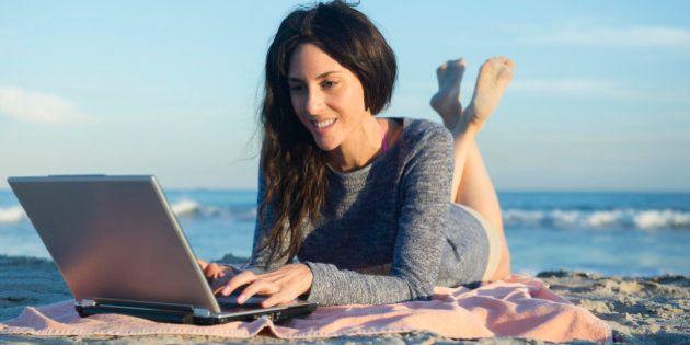 USA, New York State, Rockaway Beach, Woman using laptop on