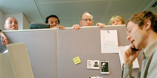 Office workers listening to male colleague on