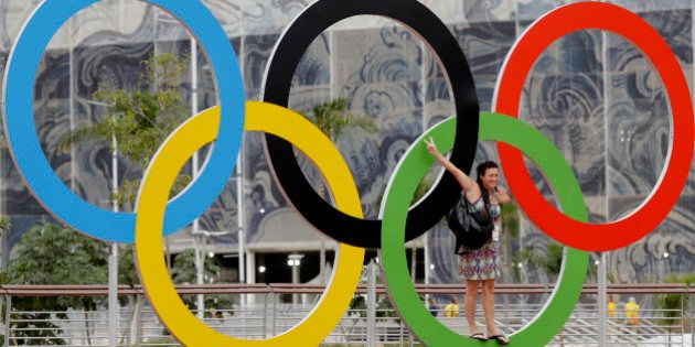 An Olympic volunteer stands on the Olympic rings as she poses for a picture prior to the Summer Olympics...