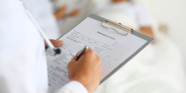 Female medicine doctor filling in patient medical history list during ward round. Medical care or insurance...