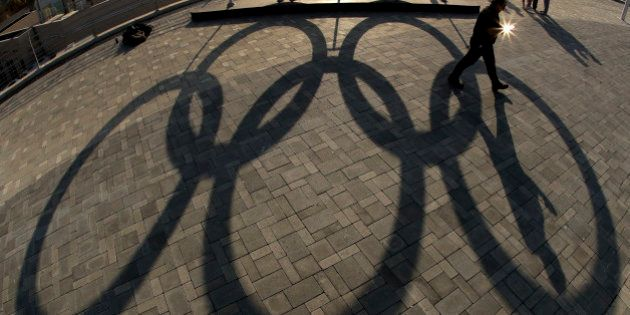 A man walks past a shadow of a set of Olympic rings in the Olympic Park ahead of the Rio 2016 Summer...